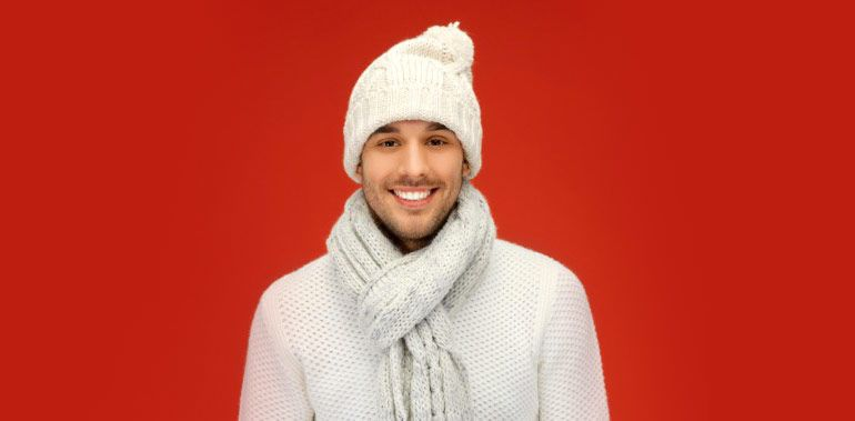 Тёплые вещи. Мужчина в белом свитере и шапке